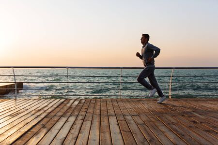 Photo for Side view of young running sportsman, during workout on quay, near the sea. Full length. - Royalty Free Image