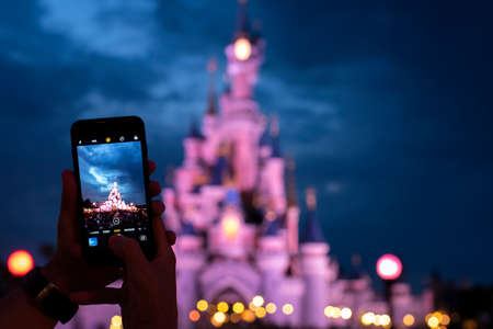 Foto per Hands taking a picture of Disney Castle - Immagine Royalty Free