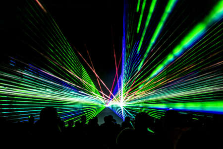Foto de Laser show rays stream. Very colorful show with a crowd silhouette and great laser rays on pyrotechnic festival in germany. - Imagen libre de derechos
