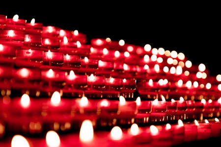 Group of red candles in church for faith resurrection prayer. Candlelight fire flames in rows are silent religion symbol for peace, life and soul. Obituary hope sacrifice against sorrows and pain.の素材 [FY310144216729]