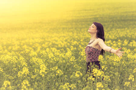 Photo for Happy beautiful woman in free summer love of youth wellbeing. Attractive young beauty girl enjoying the warm sunny sun in nature rapeseed field takes time feeling sustainability and contemplation. - Royalty Free Image