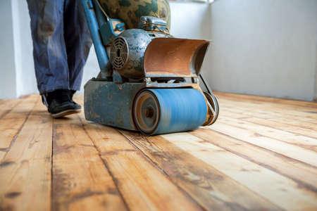 Foto de Worker polishing parquet floor with grinding machine - Imagen libre de derechos