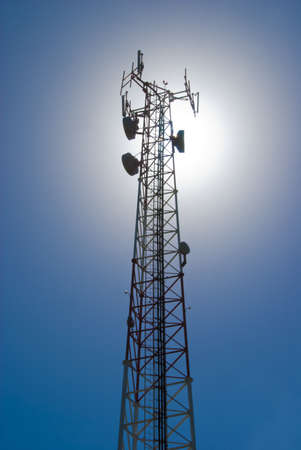Cell tower and radio antenna back lit by sun