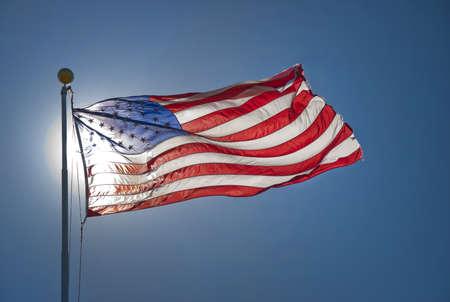 American flag back lit by sun