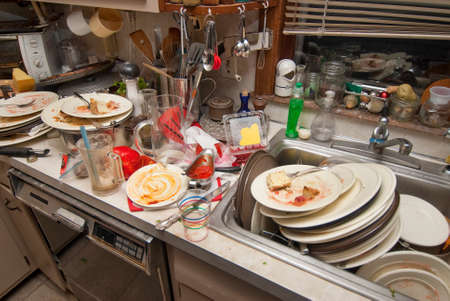 Photo pour Dirty dishes over flowing in a kitchen sink - image libre de droit