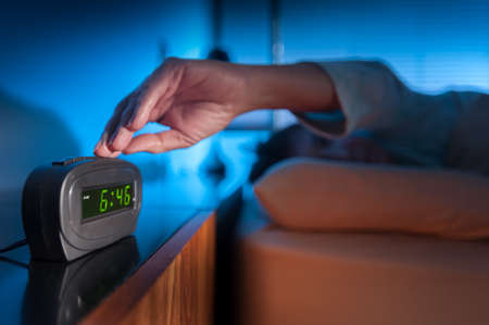 Woman pressing snooze button on early morning digital alarm clock