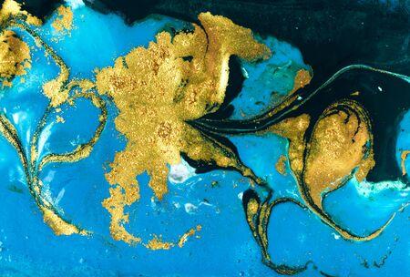 Foto de Liquid uneven blue and green marbling pattern with golden glitter and glare of light - Imagen libre de derechos