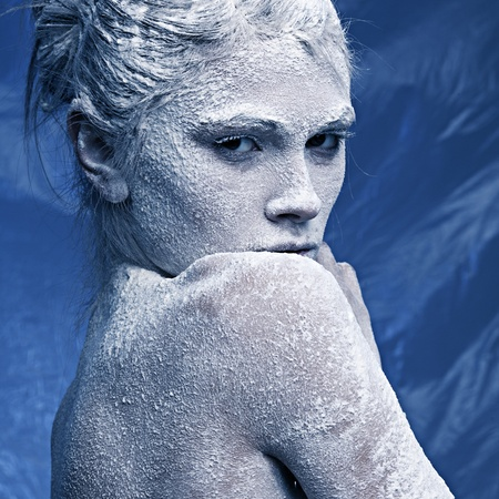 Portrait of a beautiful girl in the frost on his face on a blue ice background