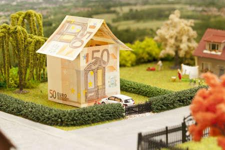 a euro bill house in a green neighbourhood scenery