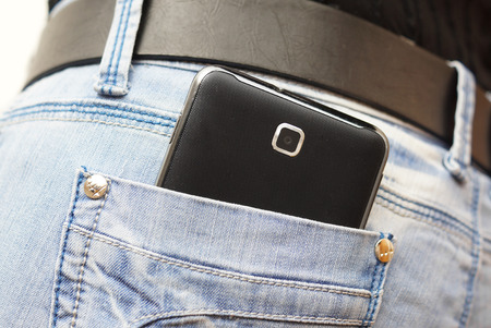 mobile phone in woman jeans pocket