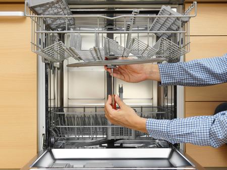 Photo pour handyman repairing a dishwasher - image libre de droit