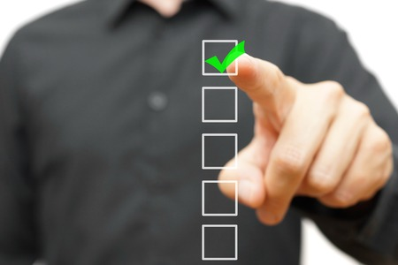 Photo pour Young businessman checking mark on checklist with marker. - image libre de droit