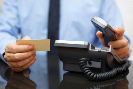 businessman holding business card and calling his client