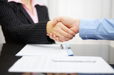 business partner and client  are handshaking over signed contract