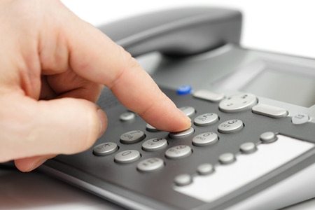 closeup of finger dialing on telephone. customer support concept
