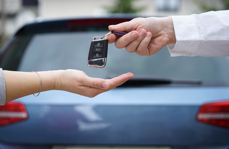 Photo pour car dealer gives the customer the car keys with car in backgorund - image libre de droit