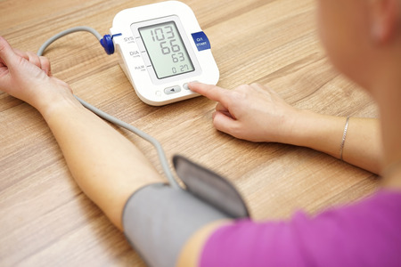 Photo pour Woman is taking care for health with hearth beat monitor and blood pressure - image libre de droit