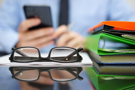businessman is calling financial adviser for help.Focus on glasses