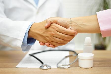 Photo pour Satisfied patient is handshaking with good doctor over good health report - image libre de droit
