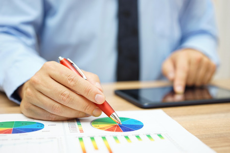 financial worker analyzing business data and working with tablet computer
