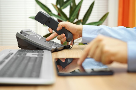 businessman working on tablet computer  is calling service for support
