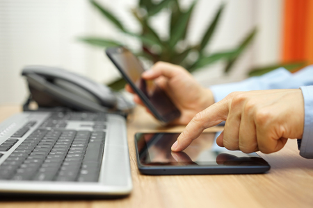 Photo pour businessman is working with tablet computer and smart mobile phone on workplace - image libre de droit