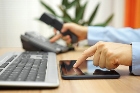 Photo pour busy businessman  with tablet computer is dialing telephone number - image libre de droit