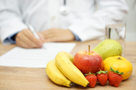 Photo for Nutritionist Doctor writing diet plan, focus on fruit and water - Royalty Free Image
