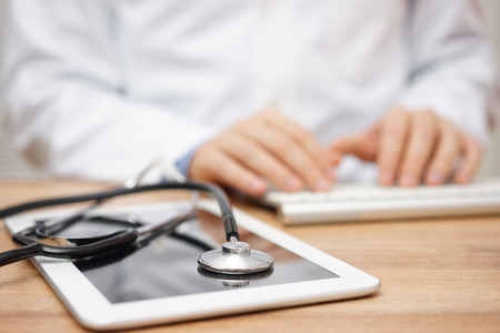 Photo pour Blurred doctor in background typing on computer keyboard with tablet and stethoscope in foreground - image libre de droit