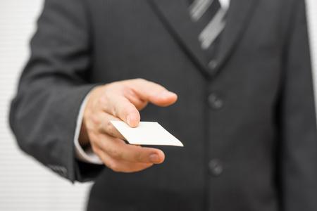Photo pour Business man handing a blank business card - image libre de droit
