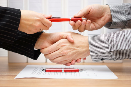 Photo pour Business partners shaking hands and exchanging pen after finished deal - image libre de droit