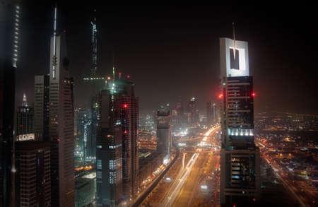 Towering city skyscraper blocks in Dubai with view of Burj