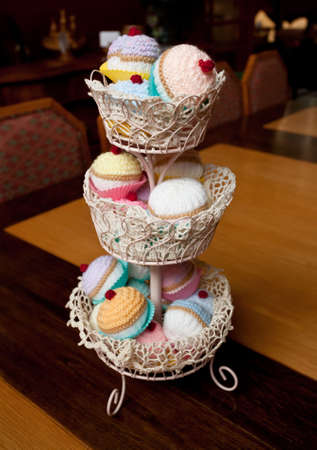 Unusual knitted or crocheted cakes and buns on a white plate