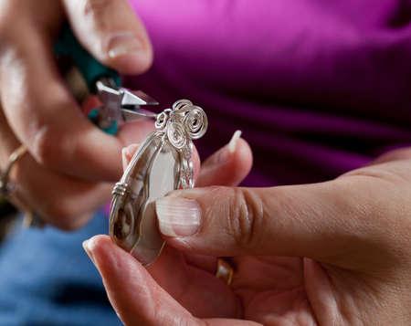 Photo pour Hands holding pliers creating silver wire wrap pendant - image libre de droit