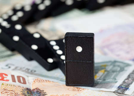 Fallen dominoes on pound, euro and dollar bank notes illustrating banking crisis