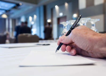 Conference table with hand taking notes or minutes with people in background