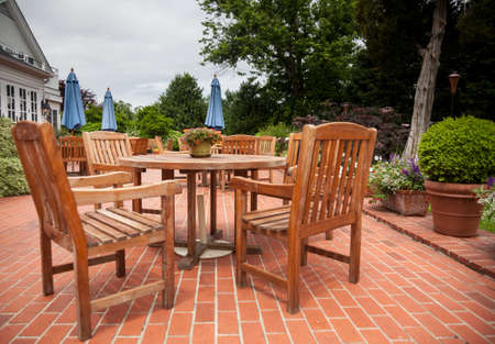 Many wooden teak tables and chairs on brick pation in cafe or restaurant
