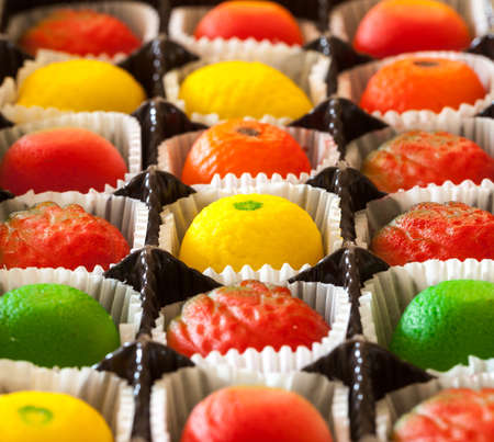 Fruit shaped candies in macro image of marzipan sweets in paper wrappings