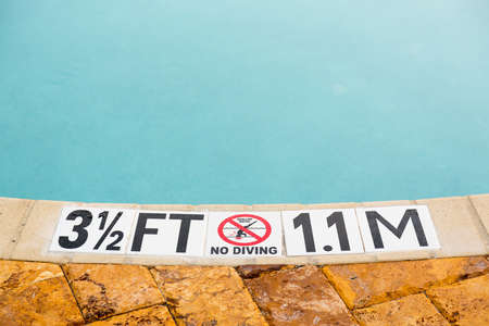 Sign showing 3.5 ft depth on edge of blue swimming pool with no diving