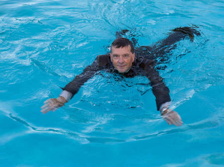 Senior caucasian businessman in suit swimming in deep blue water and smiling as he tries to keep afloat