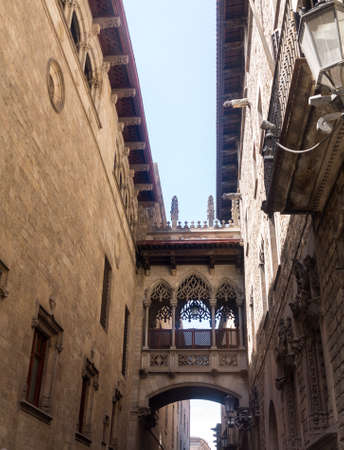 Narrow street or alley in Old Town of Barcelona with a carved bridge constructed between two old medieval homes