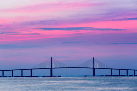 Brilliant sunrise lights up the sky behind Sunshine Skyway Bridge from St Petersburg Florida across Tampa Bay.