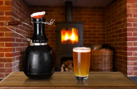 Large 64 fluid ounce four pint growler bottle with a glass of cold beer or ale in front of fire. Used by microbreweries to serve beer for home consumption