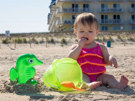 Cute caucasian baby girl on sandy beach tasting sand for the first time in Ocean CIty, Maryland, USA