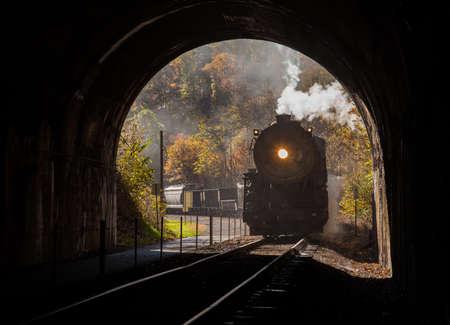 Foto de Old steam train pulling into a tunnel belching steam and smoke - Imagen libre de derechos