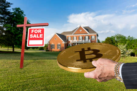 Photo pour Businessman or finance executive in suit offering bitcoin to purchase large single family home - image libre de droit
