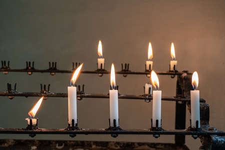 Row of prayer candles in stand against the stone wall of an old church in England