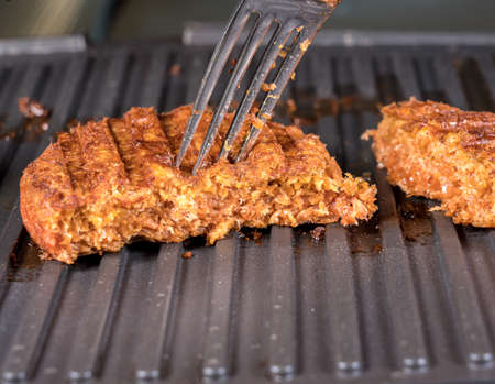 Foto per Close shot of the meat like plant-based patties for vegetarian beef burgers being grilled on hot griddle - Immagine Royalty Free