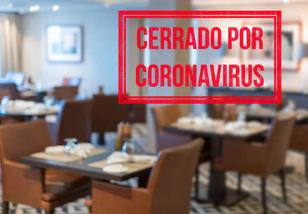 Photo for Defocused view of interior of an upmarket restaurant empty and closed with spanish notice saying Closed due to Coronavirus - Royalty Free Image