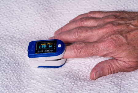 Photo pour Pulse oximeter on finger used to test blood oxygen level in case of virus infection of the lungs with senior hand resting on bedspread - image libre de droit
